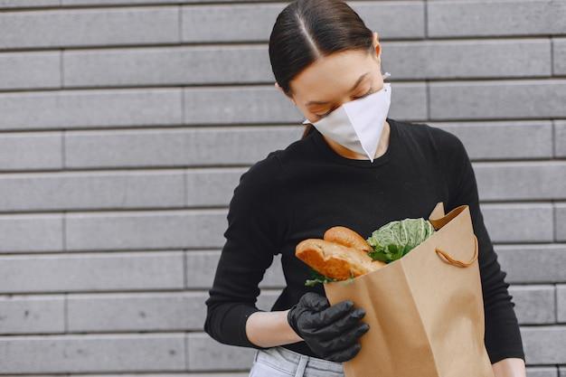 防護マスクの女の子は製品とパッケージを保持します
