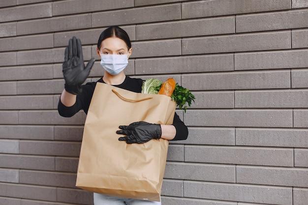 Девушка в защитной маске держит пакет с продуктами