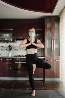 防護マスク、自宅マットの床にスポーツウェアの女の子。静けさの概念。フィットネストレーニング。