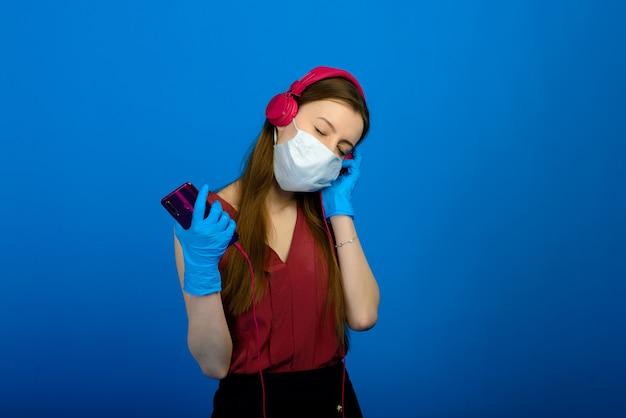 Девушка в защитной медицинской маске и голубые перчатки на голубой предпосылке. портрет женщины в прозрачной маске.