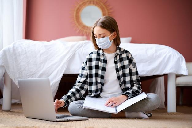 ノートパソコンで床に座って防護マスクの少女