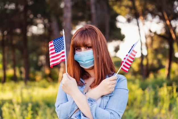 자연 속에서 손에 아메리카 합중국의 플래그와 보호 의료 마스크에 소녀. 7 월 4 일 미국 독립 기념일. 건강 보호, 안전 및 유행병 개념