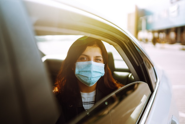 그녀의 얼굴에 보호용 살균 의료 마스크를 쓴 소녀가 택시에 앉아 있습니다.