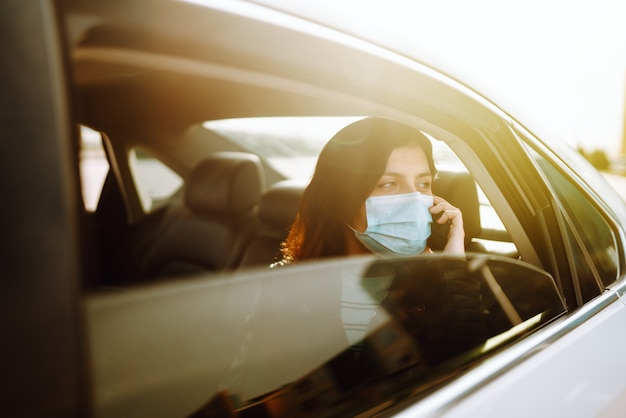 그녀의 얼굴에 보호용 살균 의료 마스크를 쓴 소녀가 택시에서 그의 전화로 이야기하고 있습니다.