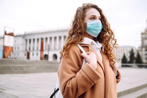 Девушка в защитной стерильной медицинской маске на лице на улице