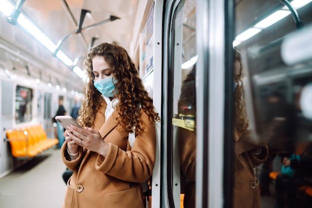 Девушка в защитной стерильной медицинской маске на лице с телефоном в вагоне метро. женщина использует телефон для поиска новостей о коронавирусе. концепция предотвращения распространения эпидемии.