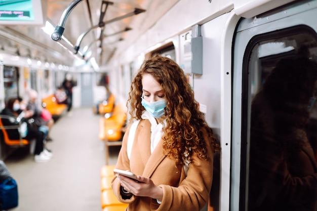 지하철 차량에서 전화로 그녀의 얼굴에 보호 멸균 의료 마스크에 소녀. 전화를 사용하여 코로나 바이러스에 대한 뉴스를 검색하는 여성. 전염병의 확산을 막는 개념.