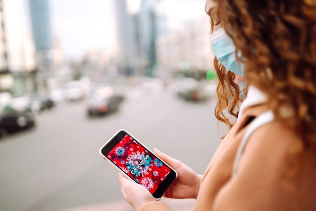 Девушка в защитной стерильной медицинской маске смотрит по телефону новости о коронавирусе.