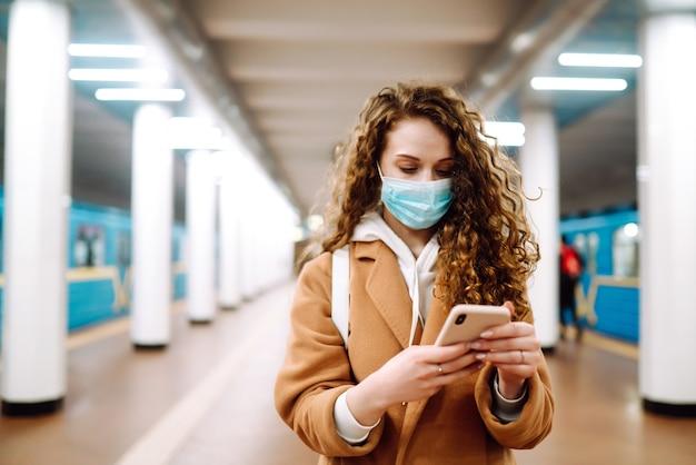 Девушка в защитной стерильной медицинской маске с телефоном на станции метро