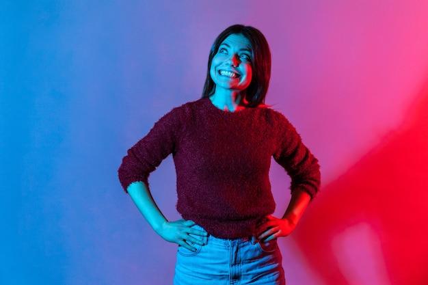 Девушка в пуловере смотрит вверх с широкой зубастой улыбкой