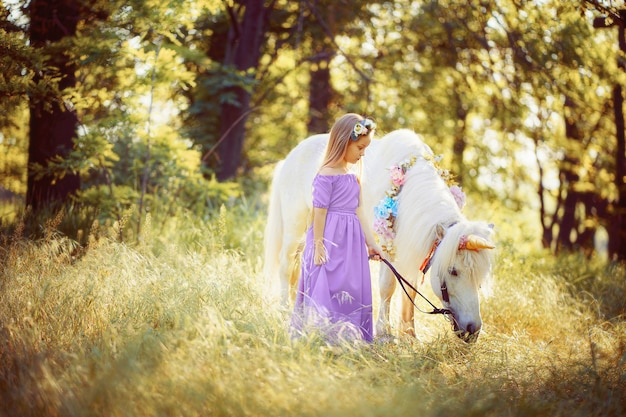 白いユニコーンの馬の夢を抱き締める紫色のドレスの女の子がtrに来る