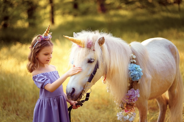 髪を抱いて、白いユニコーンにキスでユニコーンの花輪と紫色のドレスの女の子