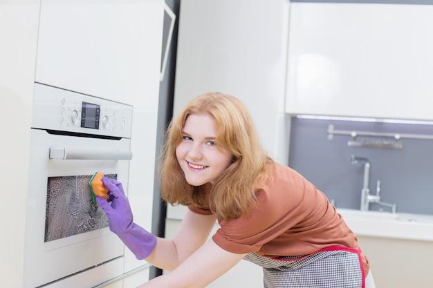 Девушка в фиолетовых перчатках моет духовку в современной кухне