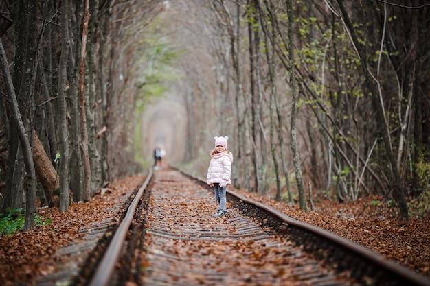 鉄道の緑のトンネルの女の子。秋の恋のトンネル。木からの鉄道とトンネル