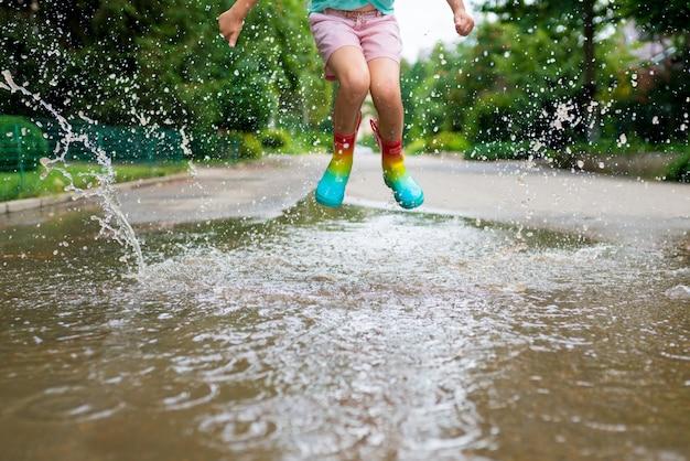 Девушка в радужных резиновых сапогах прыгает в лужах возле дома