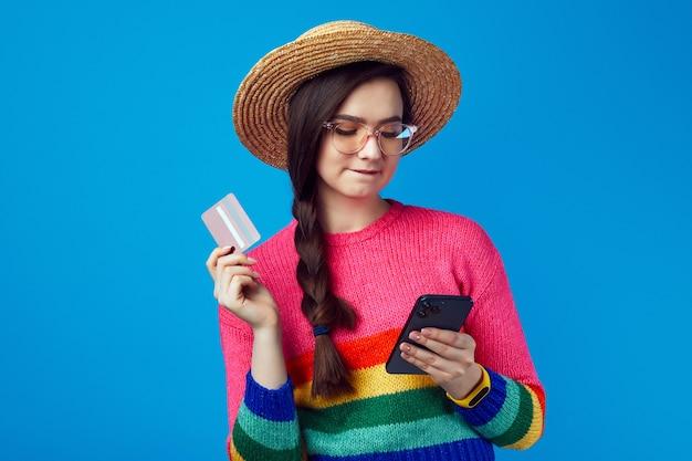 Девушка в радужном свитере и соломенной шляпе вводит данные карты в смартфон