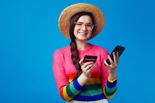 Девушка в радужном свитере держит пластиковую кредитную карту и мобильный телефон