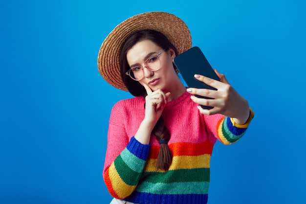 Девушка в радужном свитере держит палец на щеке и делает селфи с помощью мобильного телефона