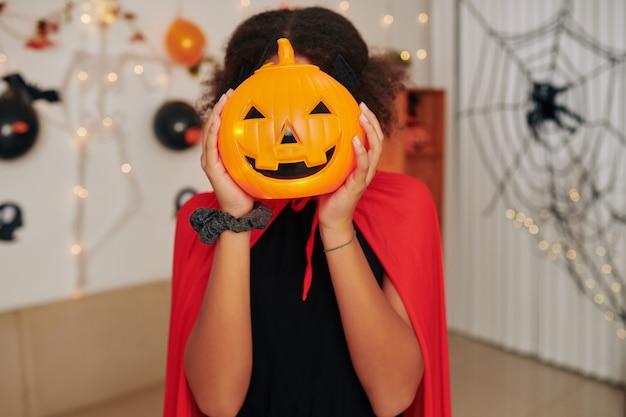 Девушка в красной накидке позирует с пластиковым фонарем jack o на вечеринке в честь хэллоуина