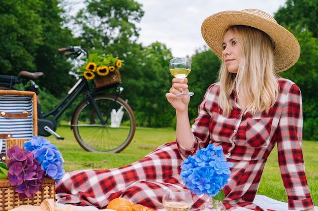 Девушка в красном клетчатом платье и шляпе сидит на вязаном одеяле для пикника, читая книгу и пьет вино.