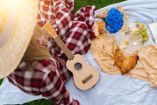 白いニットのピクニック毛布の上に座っている赤い市松模様のドレスと帽子の女の子は、ウクレレを演奏し、ワインを飲みます