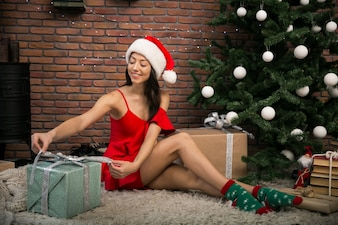 Girl in red dress on Christmas by the christmas tree