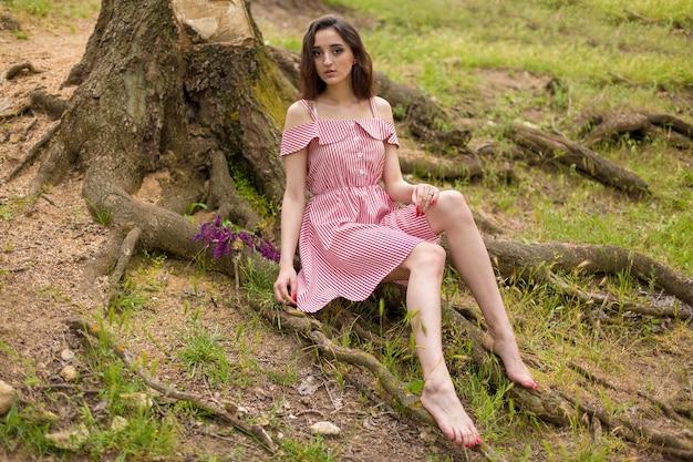 夏の自然に赤いドレスを着た少女、森の中で夏の美しい少女の肖像画