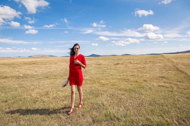 秋のフィールドに立っている赤いドレスの女の子