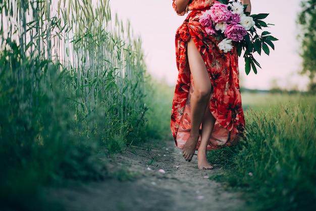 Девушка в красном платье с букетом пионов идет по тропинке босиком.