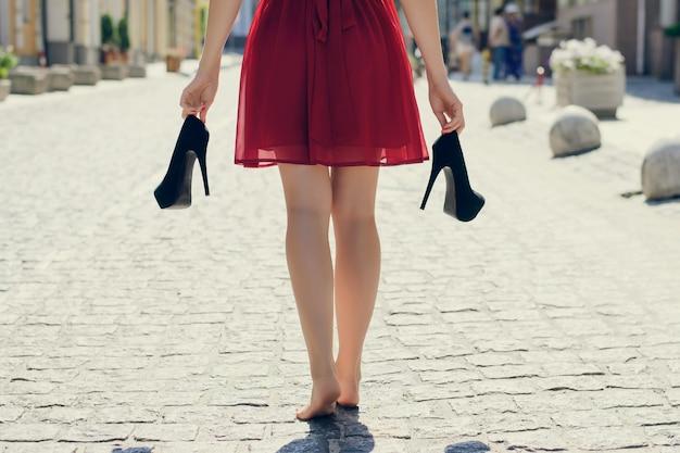 Девушка в красном платье с высокими каблуками в руках босиком