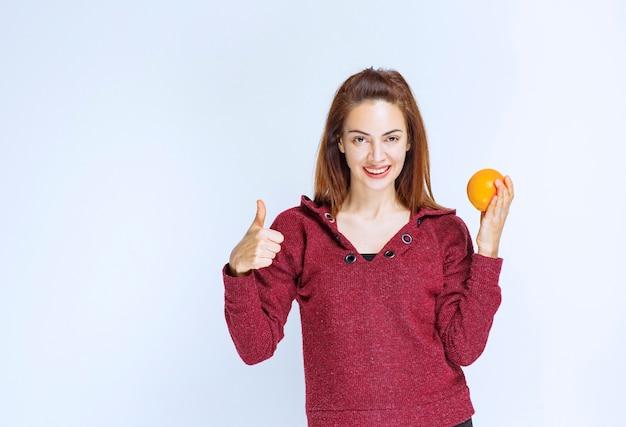 Девушка в красной куртке держит апельсин и показывает знак рукой