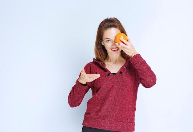 Девушка в красной куртке держит апельсин перед глазом.