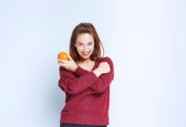 Девушка в красной куртке держит апельсин