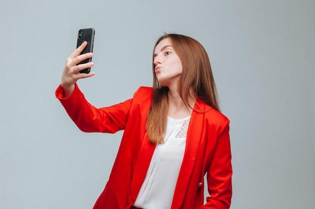 赤いジャケットの女の子が電話で自分撮りをします