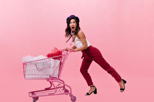 ピンクの背景の上のショッピングカートで感情的にポーズをとって赤いズボンの女の子。黒いベレー帽と夏のサンダルを履いた女性は驚いてカメラを見る。