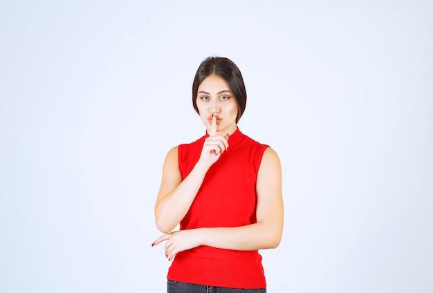 沈黙を求める赤いシャツの女の子。