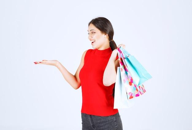 肩の後ろにカラフルなショッピング バッグを運ぶ赤いシャツの女の子。