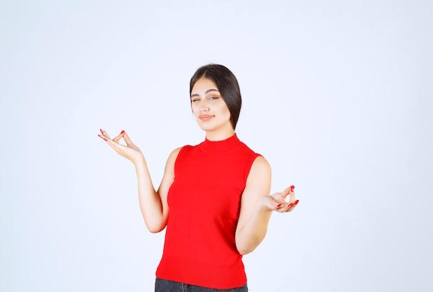 Девушка в красной рубашке делает медитацию.