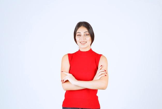 사랑스럽고 매혹적인 포즈를 취하는 빨간 셔츠의 소녀.