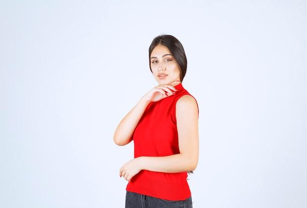 素敵で魅惑的なポーズをする赤いシャツの女の子。