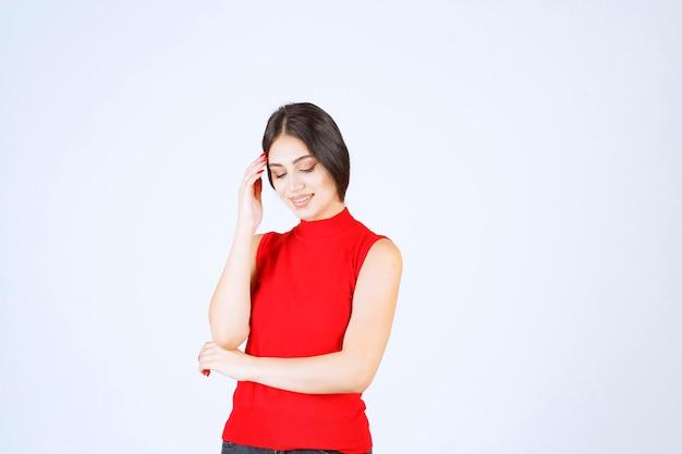 中立的でポジティブで魅力的なポーズをする赤いシャツを着た女の子。
