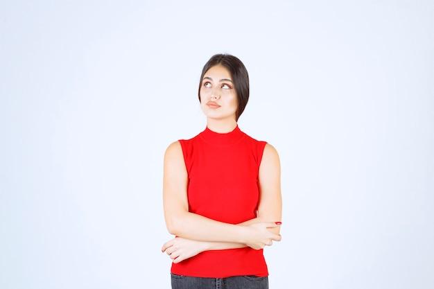 Девушка в красной рубашке дает нейтральные, позитивные и привлекательные позы.