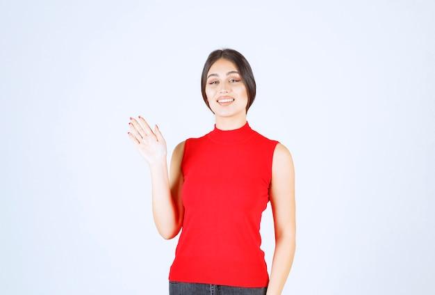 빨간색 셔츠 인사 또는 누군가 초대에 소녀.