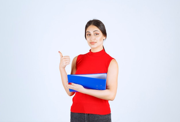 青いビジネス フォルダーを保持している赤いシャツの女の子。