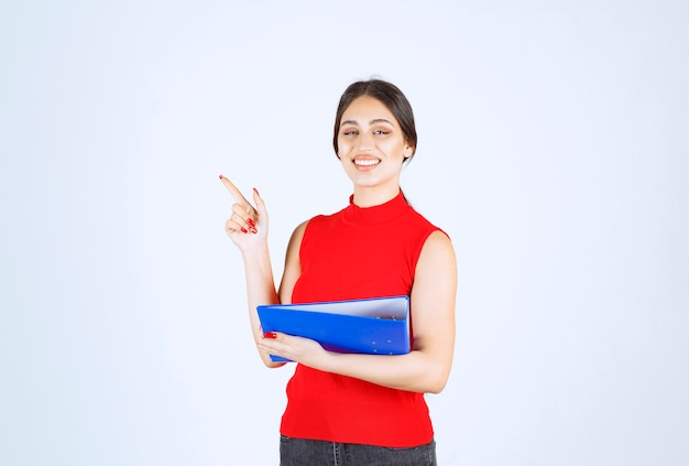 Девушка в красной рубашке держит синюю папку дела.
