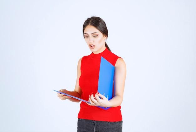 블루 비즈니스 폴더를 들고 빨간색 셔츠에 소녀.