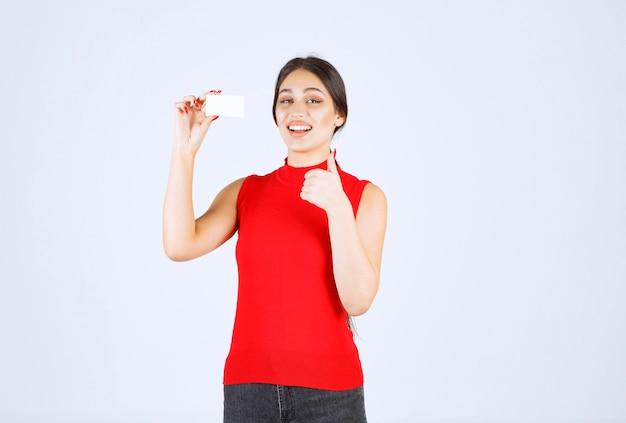 Девушка в красной рубашке держит визитную карточку и выглядит довольной.