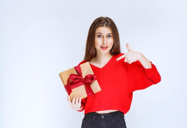 赤いリボンで包まれた段ボールのギフトボックスを保持している赤いシャツの女の子。