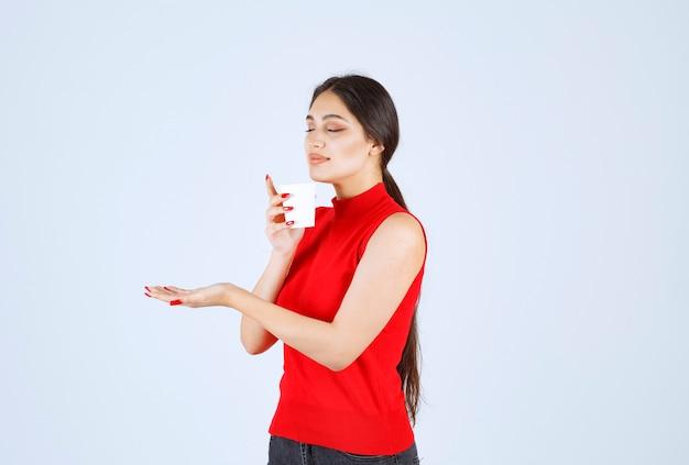 Девушка в красной рубашке держит чашку кофе и нюхает.