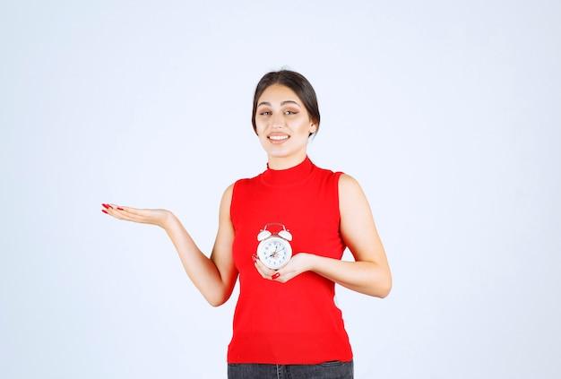 目覚まし時計を持ち、宣伝する赤いシャツを着た女の子。 無料写真